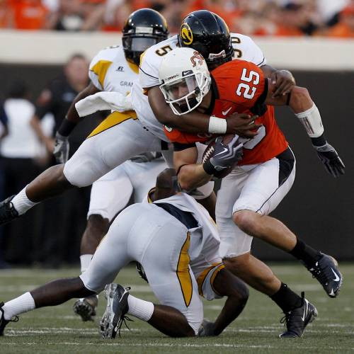 OSU's Josh Cooper (25) is tackled by Grambling's Cliff Exama (50) during the college football game between the Oklahoma State University Cowboys (OSU) and the Grambling State University Tigers (GSU) at Boone Pickens Stadium in Stillwater, Okla., Saturday, September 26, 2009. Photo by Sarah Phipps, The Oklahoman ORG XMIT: KOD