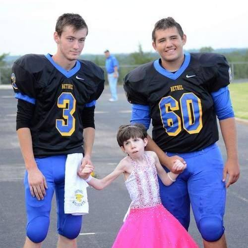 Brytni Srader is escorted by her cousin, Travis Sullivan (3), and her brother, Brady Sullivan (60), as she arrives. (Shawnee News-Star photo)