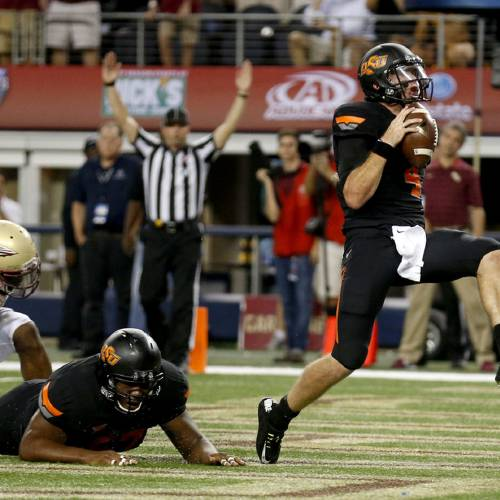 Oklahoma State's J.W. Walsh (4) celebrates a touchdown in the 4th quarter during the college football game between Oklahoma State University (OSU) and Florida State University (FSU) at the AdvoCare Cowboys Classic at At&T Stadium in Arlington, Texas, Saturday, Aug. 30, 2014. Photo by Sarah Phipps, The Oklahoman