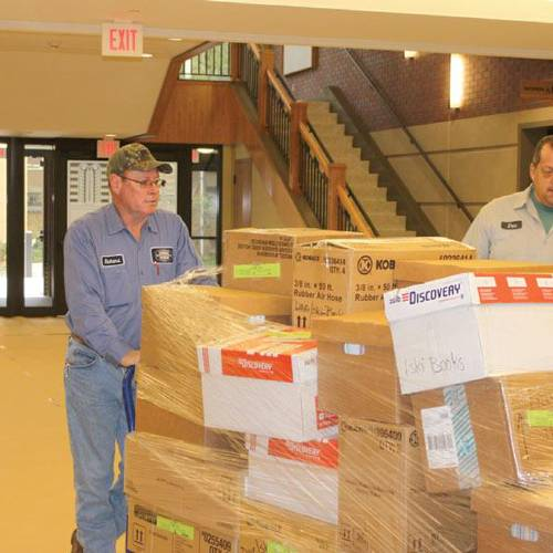 County road crewmen move pallets of boxes and furniture from one site to the next as the two-week transition into the new Rogers County Courthouse begins. (Claremore Progress photo)