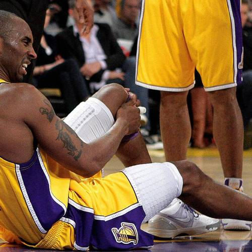 In this photo taken on Dec. 22, 2009, Los Angeles Lakers' Kobe Bryant grimaces after he came down on his knee during the second half of their NBA basketball game against the Oklahoma City Thunder in Los Angeles. Bryant likens himself to actor Bruce Willis, the action hero who can't be stopped, no matter how many injuries. The only time Bryant's broken finger, injured elbow and other maladies appear to slow him is when he's asked about them. (AP Photo/Jae C. Hong)