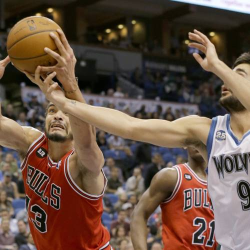 Chicago Bulls center Joakim Noah (13) pulls down a rebound against Minnesota Timberwolves guard Ricky Rubio (9), of Spain, during the fourth quarter of an NBA basketball game in Minneapolis, Wednesday, April 9, 2014. The Bulls won 102-87. (AP Photo/Ann Heisenfelt)