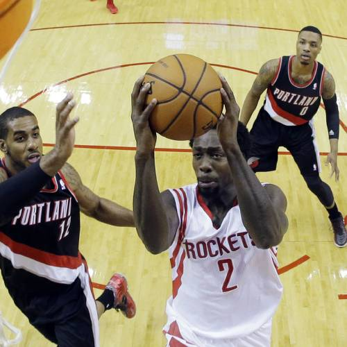 Houston Rockets' Patrick Beverley shoots past Portland Trail Blazers' LaMarcus Aldridge (12) and Damian Lillard during the first half in Game 1 of an opening-round NBA basketball playoff series, Sunday, April 20, 2014, in Houston. (AP Photo/David J. Phillip)