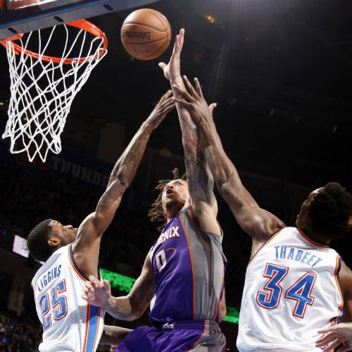 Phoenix's Michael Beasley (0) shoots in between Oklahoma City's DeAndre Liggins (25) and Hasheem Thabeet (34) during the NBA game between the Oklahoma City Thunder and the Phoenix Suns at the Chesapeake Energy Arena, Friday, Feb. 8, 2013.Photo by Sarah Phipps, The Oklahoman
