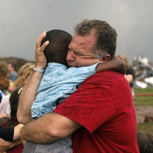 First responder Jim Routon hugs his seven year old neighbor Hezekiah as the two unite at Briarwood Elementary school after a tornado destroyed the school in south OKC Oklahoma City, OK, Monday, May 20, 2013. Near SW 149th and Hudson. PHOTO BY PAUL HELLSTERN, THE OKLAHOMAN