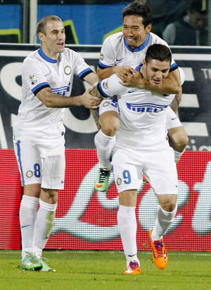 Photo - Inter Milan's Mauri Icardi, right, celebrates with teammates Rodrigo Palacio, left, and Yuto Nagatomo, on his back, after scoring during a Serie A soccer match between Fiorentina and Inter Milan, at the Artemio Franchi stadium in Florence, Italy, Saturday, Feb. 15, 2014. (AP Photo/Fabrizio Giovannozzi)