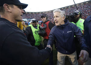Photo - San Francisco 49ers head coach Jim Harbaugh, left, shakes hands with Seattle Seahawks head coach Pete Carroll, right, at the end of an NFL football game, Sunday, Dec. 8, 2013, in San Francisco. The 49ers defeated the Seahawks 19-17. (AP Photo/Marcio Jose Sanchez)