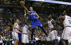 Photo - Philadelphia 76ers guard Michael Carter-Williams (1) drives through the Boston Celtics for a basket during the second half of an NBA basketball game Friday, April 4, 2014, in Boston. Carter-Williams had 24 points in the 76ers' 111-102 win. (AP Photo/Charles Krupa)