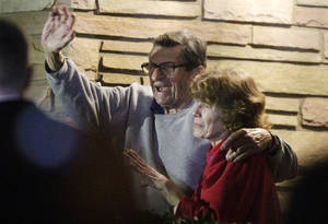 Photo - FILE - In this Nov. 9, 2011 file photo, former Penn State Coach Joe Paterno and his wife, Sue Paterno, stand on their porch to thank supporters gathered outside their home in State College, Pa. Sue Paterno says the family's detailed response to a critical report on the handling of child abuse allegations against former assistant coach Jerry Sandusky is being released to the public. (AP Photo/Gene J. Puskar, File)
