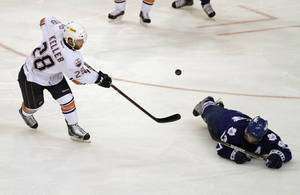 Photo - OKC's Ryan Keller, left, hits a puck past Toronto's Nazem Kadri during Game 2 of the Western Conference Finals at the Cox Convention Center on Friday. The Barons won, 5-1. Photo by Garett Fisbeck, For The Oklahoman