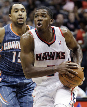 photo -   FILE - In this April 4, 2012, file photo, Atlanta Hawks' Joe Johnson, right, drives against Charlotte Bobcats' Gerald Henderson,in an NBA basketball game in Atlanta. Multiple media outlets, starting with ESPN and all citing anonymous sources, are reporting the Hawks and New Jersey Nets have agreed to a trade that would send Johnson from Atlanta to Brooklyn, Monday, July 2. (AP Photo/David Goldman, File)