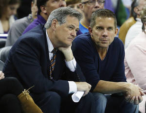 Photo - Mickey Loomis, executive vice president/general manager of the New Orleans Saints, talks with Saints head coach Sean Payton, right, in the first half of an NBA basketball game between the New Orleans Hornets and the Phoenix Suns in New Orleans, Wednesday, Feb. 6, 2013. (AP Photo/Bill Haber)