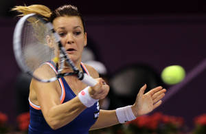 Photo - Poland's Agnieszka Radwanska returns the ball to Simona Halep of Romania during the semifinal of the WTA Qatar Ladies Open in Doha, Qatar,Saturday, Feb. 15, 2014. (AP Photo/Osama Faisal)