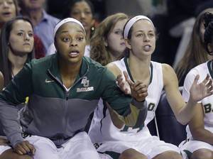 Photo - Baylor guard Odyssey Sims, left, and teammate Makenzie Robertson watch from the bench during the second half of an NCAA college basketball game against TCU, Saturday, Jan. 11, 2014, in Waco, Texas. Baylor won 80-46. (AP Photo/LM Otero)