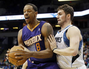 Photo - Phoenix Suns' Channing Frye, left, hangs tightly to the ball as Minnesota Timberwolves' Kevin Love  defends in the second half of an NBA basketball game  Wednesday, Jan. 8, 2014, in Minneapolis. The Suns won 104-103. Frye score 22 points while Love scored 25 and had12 rebounds. (AP Photo/Jim Mone)