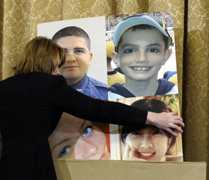 "Photo - A poster board with photos of those who died in the Boston Marathon bombing is put away during the House Homeland Security Committee at a hearing on ""The Boston Bombings: A First Look,"" on Capitol Hill in Washington, Thursday, May 9, 2013. (AP Photo/Susan Walsh)"