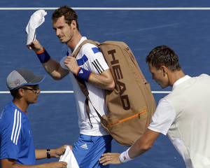 Photo - Andy Murray, from Great Britain, walks off court after losing 6-3, 6-4, to Tomas Berdych, right, from the Czech Republic, in a quarterfinal match at the Western & Southern Open tennis tournament, Friday, Aug. 16, 2013, in Mason, Ohio. (AP Photo/Al Behrman)