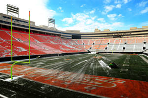 Photo - The Oklahoma State University athletic department cleared the snow from Boone Pickens Stadium on Friday, using small tractors to clear the field. Photo by KT King, Tulsa World <strong>KT King</strong>