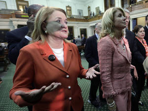 Photo - Sen. Sylvia Garcia, D-Houston, left, throws up her hands as she leaves the Senate Chamber with Sen. Wendy Davis, D-FortWorth, right, after the Texas Senate passed an abortion bill, Friday, July 12, 2013, in Austin, Texas. The bill will require doctors to have admitting privileges at nearby hospitals, only allow abortions in surgical centers, dictate when abortion pills are taken and ban abortions after 20 weeks. (AP Photo/Eric Gay)