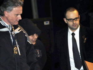 Photo - In this Saturday, Dec. 29, 2012 photo, New York City Police Department detectives escort Erika Menendez, second from left, out of the 112th Precinct in the Queens borough of New York. Menendez was arraigned Saturday night on a charge of murder as a hate crime. Judge Gia Morris has ordered that the 31-year-old be held without bail and be given a mental health exam. (AP Photo/Newsday, Danielle Finkelstein) NYC LOCALS OUT