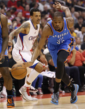 Photo - Oklahoma City's Kevin Durant (35) goes past Los Angeles' Matt Barnes (22) during Game 4 of the Western Conference semifinals in the NBA playoffs between the Oklahoma City Thunder and the Los Angeles Clippers at the Staples Center in Los Angeles, Sunday, May 11, 2014. Photo by Nate Billings, The Oklahoman