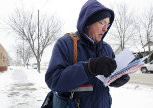 photo - Mail carrier Bruce Nicklay walks along East Third Street in Winona, Minn., delivering letters to homes Wednesday, Feb. 6, 2013. The U.S. Postal Service will stop delivering mail on Saturdays but continue to deliver packages six days a week under a plan aimed at saving about $2 billion annually, the financially struggling agency says. (AP Photo/Winona Daily News, Andrew Link)