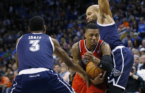 Photo - Portland Trail Blazers guard Damian Lillard (0) drives between Oklahoma City Thunder forward Perry Jones (3) and guard Derek Fisher (6) during the second quarter of an NBA basketball game in Oklahoma City, Tuesday, Dec. 31, 2013. (AP Photo/Sue Ogrocki)