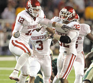 Photo - Austin Box (12) and Jamell Fleming (32) celebrate after Box stopped Baylor running back Jay Finley on a fourth and one to give the Sooners the ball inside Baylor teritory during the first half of the college football game between the University of Oklahoma Sooners (OU) and the Baylor Bears (BU) at Floyd Casey Stadium on Saturday, November 20, 2010, in Waco, Texas.   Photo by Steve Sisney, The Oklahoman