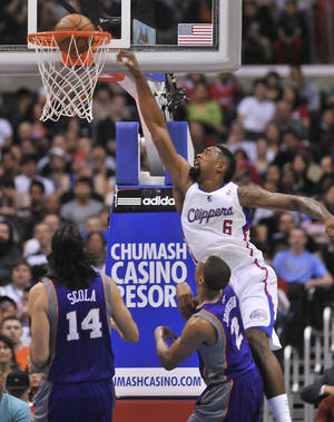 Photo - Los Angeles Clippers center DeAndre Jordan (6) throws down a dunk in front of Phoenix Suns forward Luis Scola (14), of Argentina, and forward Wesley Johnson (2) in the first half of an NBA basketball game in Los Angeles on Wednesday, April  3, 2013. (AP Photo/Richard Hartog)