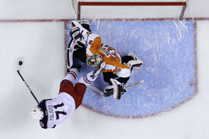 Photo - Columbus Blue Jackets' Nick Foligno, left, tries to get a shot past Philadelphia Flyers goalie Steve Mason during the first period of an NHL hockey game, Thursday, April 3, 2014, in Philadelphia. (AP Photo/Matt Slocum)