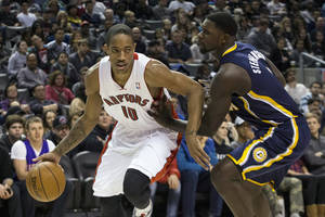 Photo - Toronto Raptors' DeMar DeRozan, left, drives at Indiana Pacers' Lance Stephenson during the first half of an NBA basketball game in Toronto on Wednesday, Jan. 1, 2014. (AP Photo/The Canadian Press, Chris Young)