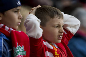 Photo - A young Liverpool supporter watches as his team is beaten by Chelsea in their English Premier League soccer match at Anfield Stadium, Liverpool, England, Sunday April 27, 2014. (AP Photo/Jon Super)