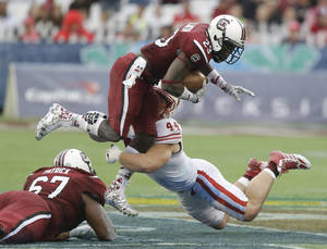 Photo - South Carolina wide receiver Bruce Ellington (23) is stopped by Wisconsin linebacker Chris Borland (44) after a reception during the second half of the Capital One Bowl NCAA college football game in Orlando, Fla., Wednesday, Jan. 1, 2014. South Carolina won the game 34-24.(AP Photo/John Raoux)