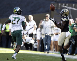 Photo - Colorado wide receiver Paul Richardson, right, pulls in a pass for a long gain in front of Oregon cornerback Terrance Mitchell in the first quarter of an NCAA college football game in Boulder, Colo., on Saturday, Oct. 5, 2013. (AP Photo/David Zalubowski)