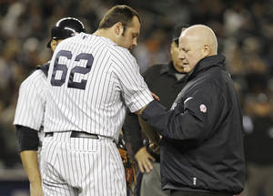 Photo -   A trainer looks at the arm of New York Yankees' Joba Chamberlain (62) after Chamberlain was hit by a broken bay during the twelfth inning of Game 4 of the American League division baseball series against the Baltimore Orioles Thursday, Oct. 11, 2012, in New York. (AP Photo/Kathy Willens)