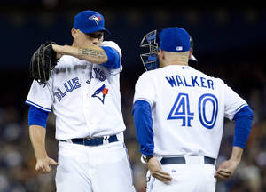 Photo - Toronto Blue Jays starting pitcher Dustin McGowan, left, looks on as pitching coach Pete Walker (40) makes a trip to the mound during first inning AL baseball action against the New York Yankees in Toronto on Friday, April 4, 2014.  (AP Photo/The Canadian Press,Peter Power)