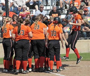 Photo - Davenport  softball center fielder Annie Waters, right, hops onto home base to score as her team mates greet her during a game with Sterling, Friday, October 11, 2013.  Photo by David McDaniel, The Oklahoman