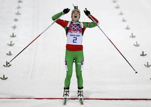 Photo - Belarus' Darya Domracheva celebrates winning the gold medal in the women's biathlon 12.5k mass-start, at the 2014 Winter Olympics, Monday, Feb. 17, 2014, in Krasnaya Polyana, Russia. (AP Photo/Kirsty Wigglesworth)