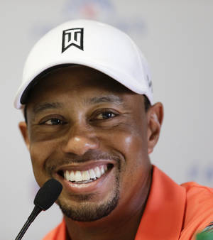 Photo - Tiger Woods talks to the media during a news conference at the Farmers Insurance Open golf tournament at Torrey Pines Golf Course on Wednesday, Jan. 22, 2014, in San Diego. (AP Photo/Chris Carlson)