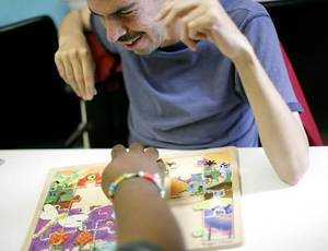 photo - Michael  Avila, 38, works on a children&#039;s puzzle with a friend at Metropolitan Better Living Center in Oklahoma City on Tuesday, June 9, 2009.  Michael, who has cerebral palsy and can&#039;t speak, works puzzles everyday with another man who can&#039;t speak. Photo by John Clanton