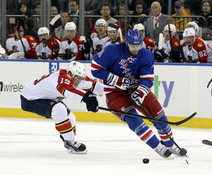 Photo - CORRECTS ID TO RICK NASH- Florida Panthers' Scottie Upshall (19) battles for the puck against New York Rangers' Rick Nash during the second period of an NHL hockey game Thursday, April 18, 2013 at Madison Square Garden in New York. (AP Photo/Mary Altaffer)