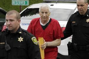 Photo - Former Penn State University assistant football coach Jerry Sandusky, center, arrives for sentencing at the Centre County Courthouse in Bellefonte, Pa., Tuesday, Oct. 9, 2012. Tuesday, Oct. 9, 2012. Sandusky was convicted of sexually abusing 10 boys in a scandal that rocked the university and brought down Hall of Fame coach Joe Paterno. (AP Photo/Gene J. Puskar