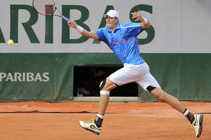 Photo - John Isner of the U.S. returns the ball during the first round match of the French Open tennis tournament against France's Pierre-Hugues Herbert at the Roland Garros stadium, in Paris, France, Sunday, May 25, 2014. (AP Photo/David Vincent)