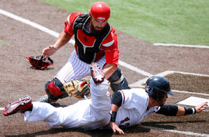 Photo - San Diego State's Tim Zier, bottom, is tagfed out at home plate by Louisiana-Lafayette catcher Michael Strentz, top, in the first inning of an NCAA college baseball tournament regional game in Lafayette, La., Saturday, May 31, 2014. (AP Photo/Jonathan Bachman)