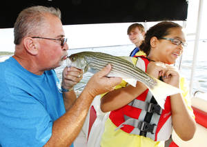 Photo - Stewart Matheson shows Kacey Guerro-Hawkins, 14, how to kiss the fish she caught while fishing during Camp Cavett at Lake Texoma.  <strong>David McDaniel - The Oklahoman</strong>