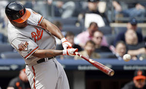 Photo - Baltimore Orioles Delmon Young connects for a fourth-inning RBI single off New York Yankees starting pitcher Ivan Nova in a baseball game against the New York Yankees at Yankee Stadium in New York, Tuesday, April 8, 2014.  (AP Photo/Kathy Willens)