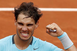 Photo - Spain's Rafael Nadal clenches his fist after defeating Austria's Dominic Thiem during the second round match of  the French Open tennis tournament at the Roland Garros stadium, in Paris, France, Thursday, May 29, 2014. Nadal won 6-2, 6-2, 6-3. (AP Photo/Darko Vojinovic)