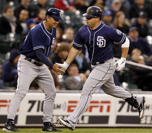 Photo -   San Diego Padres' Yonder Alonso, right, is congratulated by third base coach Glenn Hoffman on a home run against the Seattle Mariners in the seventh inning of a baseball game Wednesday, June 13, 2012, in Seattle. (AP Photo/Elaine Thompson)