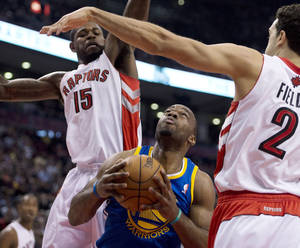 photo - Golden State Warriors forward Carl Landry, bottom, tries to find a way to the basket past Toronto Raptors forward Amir Johnson (15) and Landry Fields (2) during the first half of their NBA basketball game, Monday, Jan. 28, 2013, in Toronto. (AP Photo/The Canadian Press, Frank Gunn)