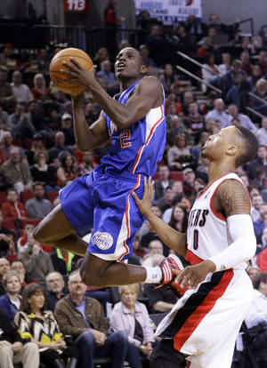 Photo - Los Angeles Clippers guard Darren Collison, left, drives to the basket past Portland Trail Blazers guard Damian Lillard during the first half of an NBA basketball game in Portland, Ore., Wednesday, April 16, 2014. (AP Photo/Don Ryan)